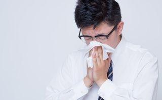 花粉症で鼻をかむ男性