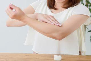 保湿剤を腕に塗り込む女性