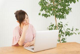 パソコンを見て考え込む女性